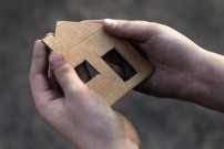 homeless boy holding a cardboard house, dirty hand