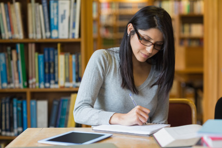 female student studying in library (shutterstock)