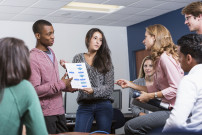Multi-ethnic group of high school or university students and female teacher at school in classroom.  Two students standing up, giving presentation to class.  Main focus on the students holding the chart.