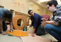 A teacher offers advice as two engineering students stain the animal house they built.  Photo by Allison Shelley/The Verbatim Agency for American Education: Images of Teachers and Students in Action